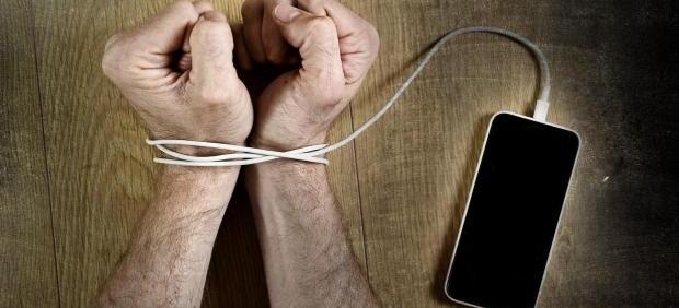 스마트폰 케이블에 손이 묶인 사진